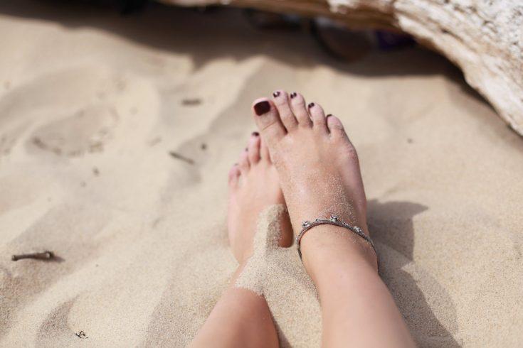 human feet on white sand during daytime